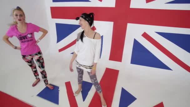 Vtipné dívky tanečnice zírat na kameru a pohybovat se v bílém studio s velkým Uk vlajka