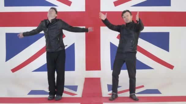 zwei süße Männer in schwarzen Motorradjacken tanzen und singen vor der Kamera.