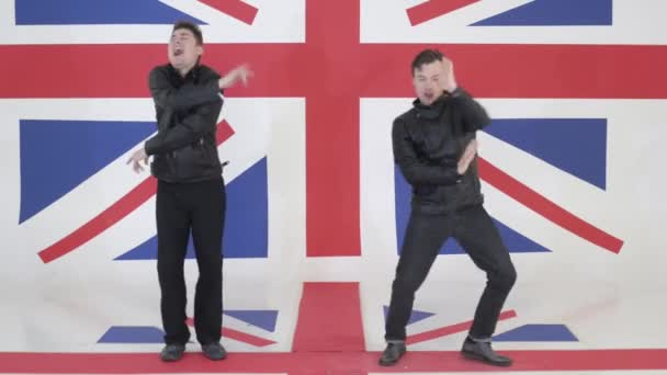 Two cute guys in black leather motorcycle jackets synchronically dance and sing