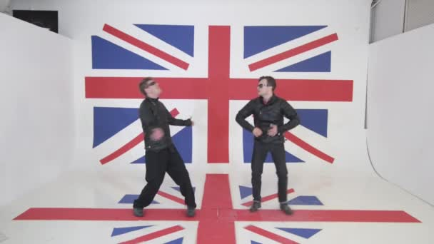 schöne künstlerisch kaukasische dunkelhaarige Männer mit Sonnenbrille in schwarzen Motorradjacken aus Leder mit Hose tanzen aktiv vor der Kamera im Studio vor dem Hintergrund einer großen britischen Flagge.