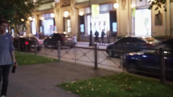 Muž v šedém svetru chodí v ulici a bere cigareta z druhé mans ústa