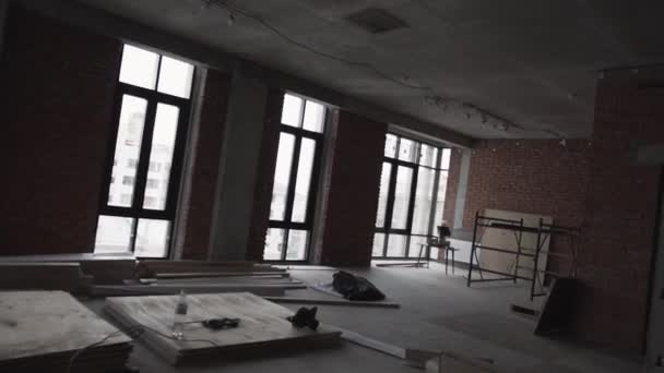 Dark apartment with big black framed windows, planks on floor and scaffolding
