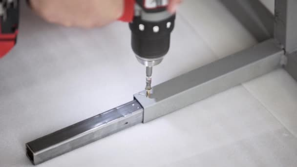 Camera shows mans hand holding and working with electric screwdriver.