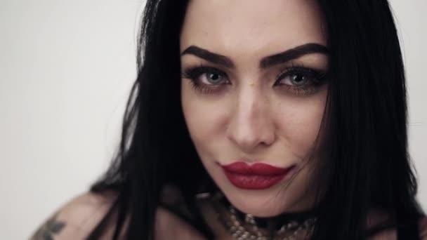 Szexi sötét hajú nő öltözve bőr tetoválás és nagy érzékeny ajkak.