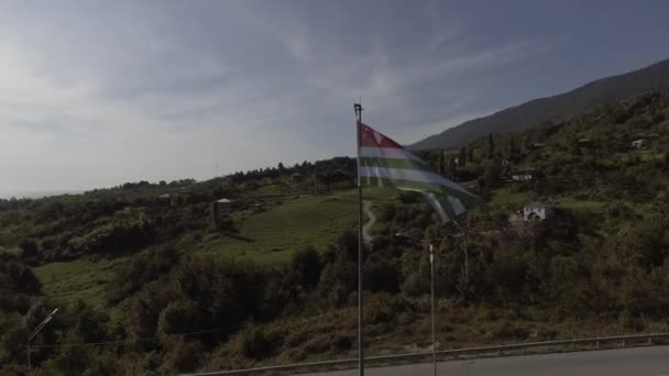 Top view of waving flag of Abkhazia on background of rural road on sunny day