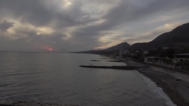 Nádherné scenérie moře, pobřeží, zelené kopce při západu slunce s oblohou.