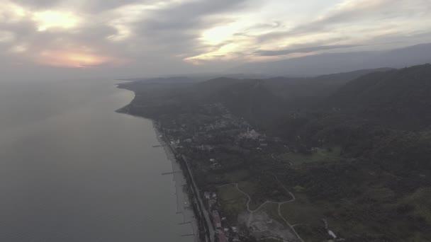 Drone telecamera mostra il Mar Nero, linea di costa, collina verde al tramonto con il cielo nuvoloso