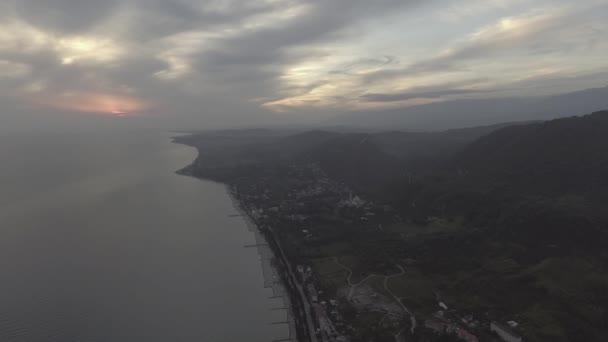 Nádhernou krajinu, moře, pobřeží, zelené kopce při západu slunce s oblohou.