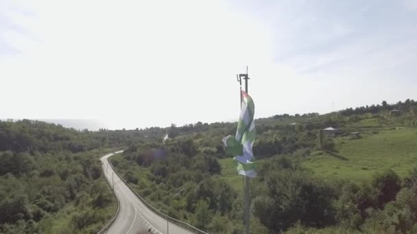 Top view of waving flag of Abkhazia in wind on background of road on sunny day