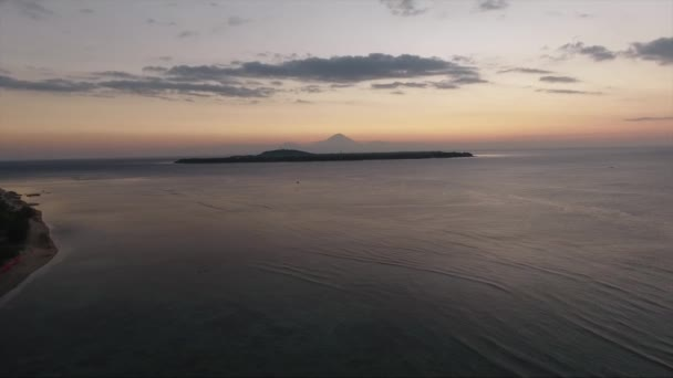 Aerial of sea with still water reflecting clear sky at sunset in summer time.