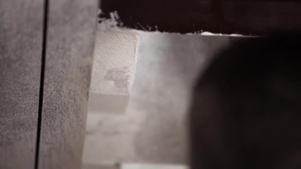 Hände männlicher Arbeiter streichen professionell graue Wände in Weiß mit großem Pinsel