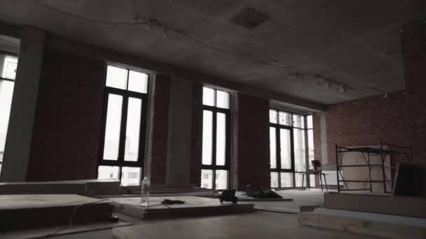 Tmavý velký sál s velkým černým rámu okna, prkna na podlahu a lešení