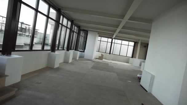 Velký prázdný byt s velkými černými orámovaný windows, šedá podlaha a bílé stěny a strop bez nábytku a lidé za denního světla