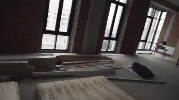 Tmavý velký pokoj s velkým černým rámu okna, prkna na podlahu a lešení