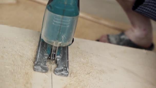Prozess der grünen staubigen elektrischen Stichsäge Schneiden von Holzplanken in der Werkstatt.