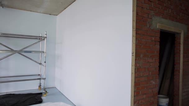 Grande vuoto luminoso appartamento con finestre incorniciate, pareti bianche e ponteggi