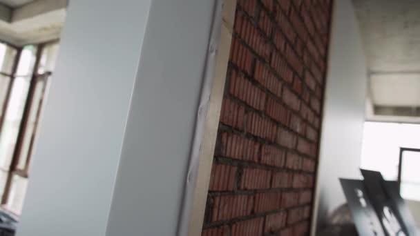 Grande corridoio vuoto in appartamento con grandi finestre con cornice nere, pavimento grigio, bianco, sfondi, muro di mattoni rosso con tubi e fili più ponteggi metallici alla luce del giorno.