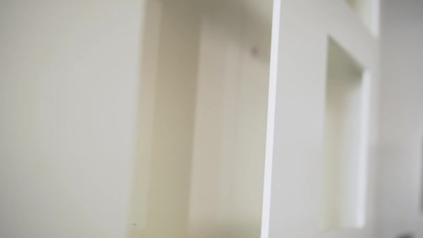 Camera shows white plastic frames of windows and doors in room.
