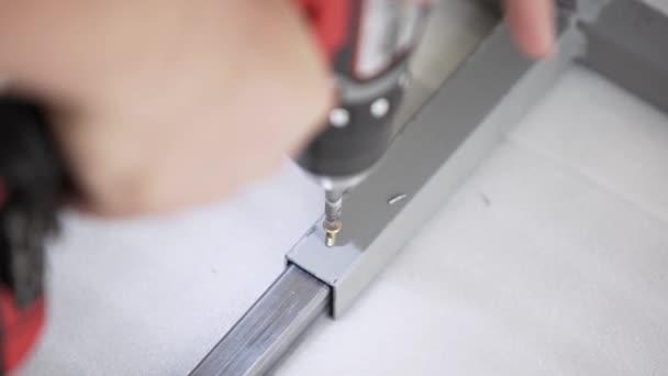 Kamera zeigt, wie man die Hand hält und mit einem Elektroschrauber arbeitet.