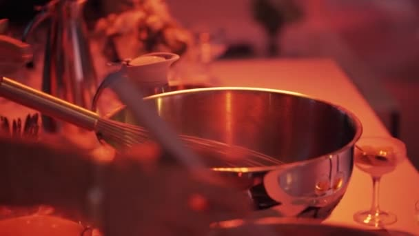 Process of whisking by hand in big steel bowl on large table at restaurant.