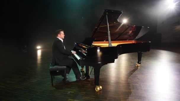 Alten altmodischen Pianist in Anzug und Hemd spielt schwarz Flügel auf der großen Bühne