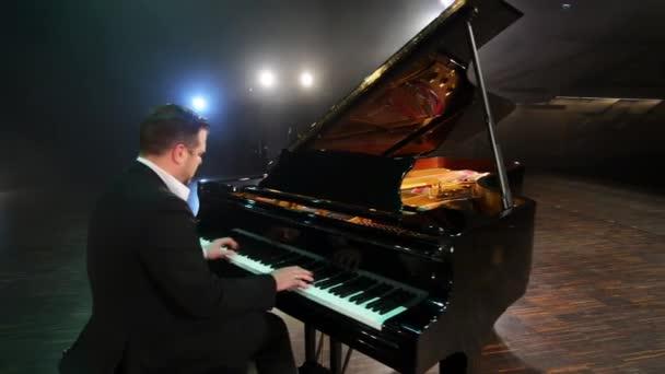 Érett szakállas zongorista öltöny és ing fekete zongora játszik a nagy színpadon.