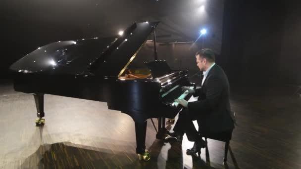 Szakállas zongorista öltöny és ing játszik gyönyörű fekete zongora a nagy színpadon
