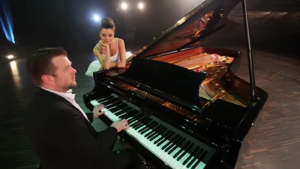 Männliche Pianist spielt süßen klassischen Flügel, weiblichen Balletttänzer neben ihm