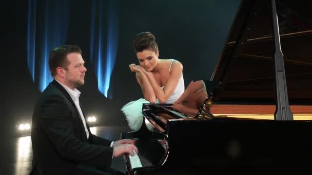Schöne Reife bärtigen männlichen Pianist im dunklen Anzug und klassisches Hemd spielt schwarze Flügel auf der großen Bühne und hübschen weiblichen Ballett-Tänzerin im Konzertsaal mit gedimmten Licht neben ihm steht