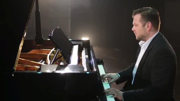 Régi vágású zongorista öltöny és ing fekete zongora játszik a nagy színpadon.