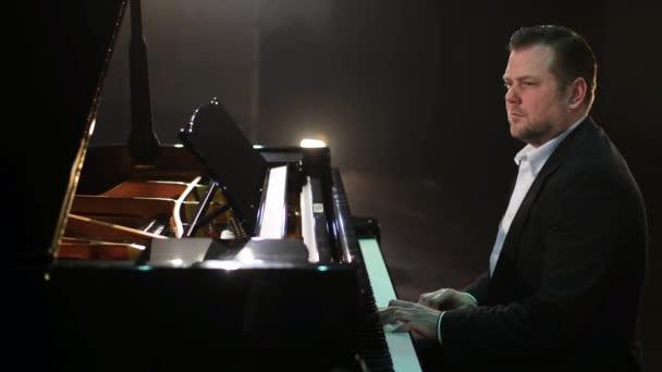 Régi vágású kaukázusi vonzó férfi zongorista sötét öltöny és a klasszikus ing játszik beautiufl fekete zongora a nagy színpadon koncertterem halványan fény.