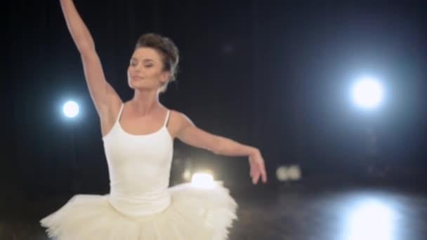 Hezká mladá ballerin expresivně a aktivně tancuje balet na velké tmavé scéně.