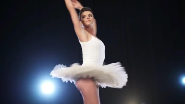 schöne junge Ballerina tanzt anmutig Ballett auf großer dunkler Bühne.