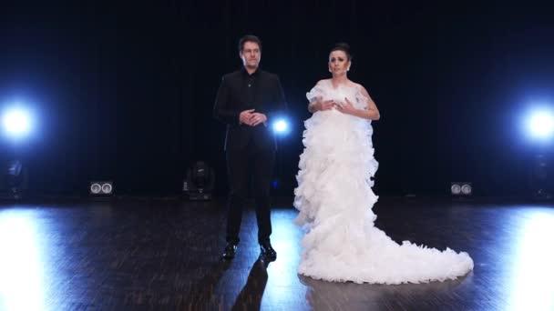 Charismatický stylové muže v černém obleku a okouzlující žena v bílých šatech zpívat.