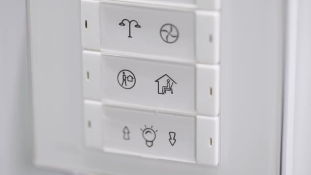 Panoramic slow view of rectangular shaped white framed electronic pad with buttons and symbols mounted to light wall and showing some functionality list icons.