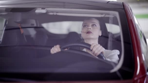 Pretty woman wearing white shirt sits in red car behind steering wheel