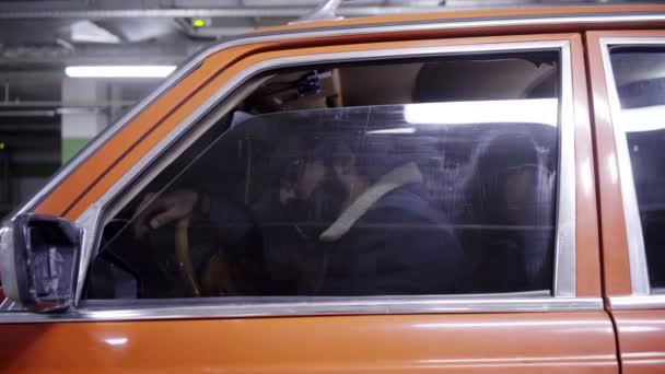 Roztomilý vousáč s dlouhými tmavými vlasy červené auto okno se otevře a začne mluvit.