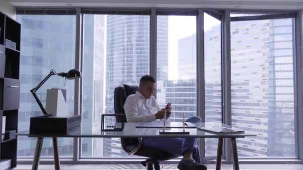 Vonzó barna férfi fehér ing mögött ül üveg íróasztal modern irodai