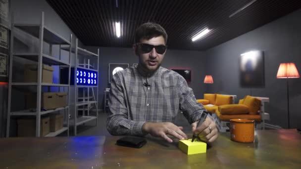 Junger Mann schreibt etwas auf gelbem Papier auf und steckt es in schwarzes Portemonnaie