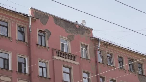 Daylight view of old pink historical building with several windows on sunny day