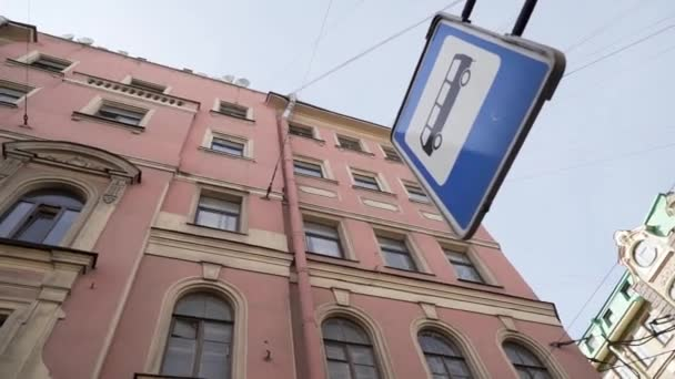 Facades of old historical building with several windows next to bus stop sign