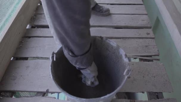 Arbeiterhände entfernen mit Pinsel nasse Betonmasse aus Eimer