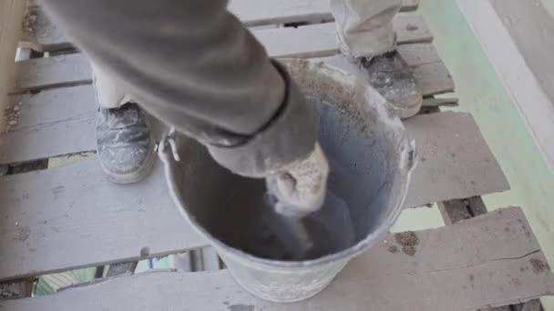 Arbeiterhände mischen nasse Betonmasse mit Pinsel in Eimer