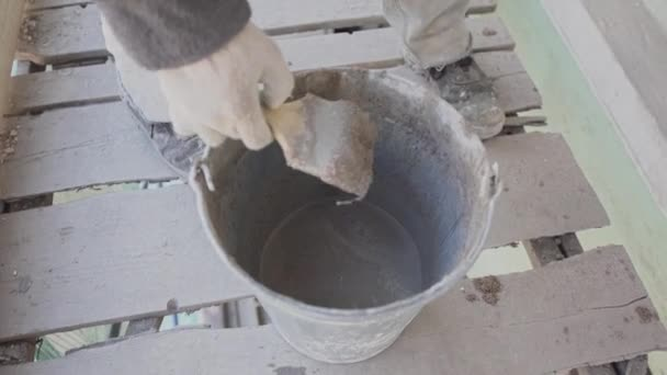 Construction worker takes out wet concrete mass with paint brush from bucket