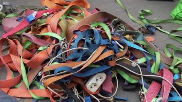 Orange, green, red, pink, grey and blue belts and ribbons are strewn on  ground