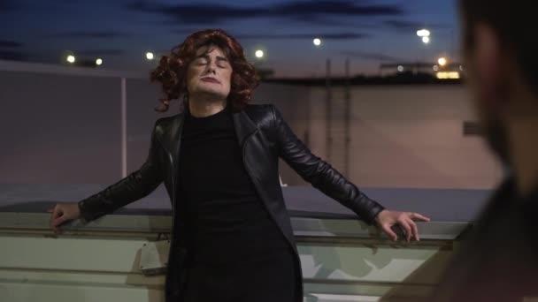 Charismatický chlapík oblečený jako ženská, nosí černé šaty a paruku, zpívá venku