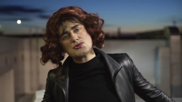 Tvář vtipného muže, oblečeného jako žena, s make-up, černými šaty a parukou.