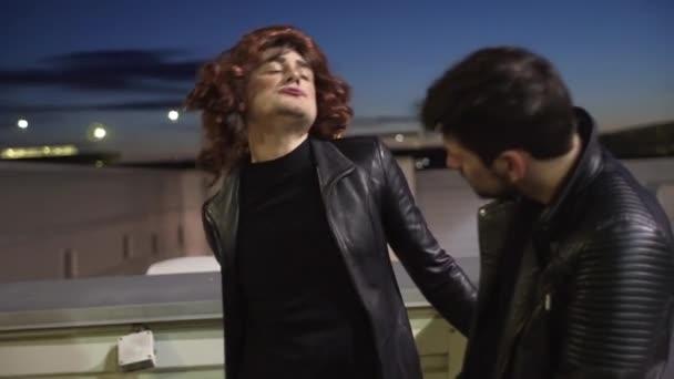 Charismatický muž oblečený jako ženská s parukou emocionálně vedle jiného muže.