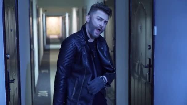 Charismatický chlapík s falešným plnovousem v jaketu tančí v úzkém koridoru mezi dveřmi