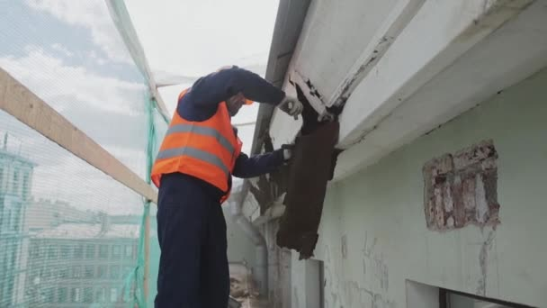 SAINT PETERSBURG, RUSSIA - APRIL 10, 2018: Building asian laborer in orange safety outfit breaks dirty old wooden wall.